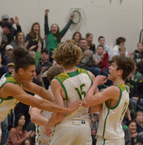 Jalen Skalskiy and Bryce Henry running up to Noah Haaland after Haaland laid the ball up and got an and one.