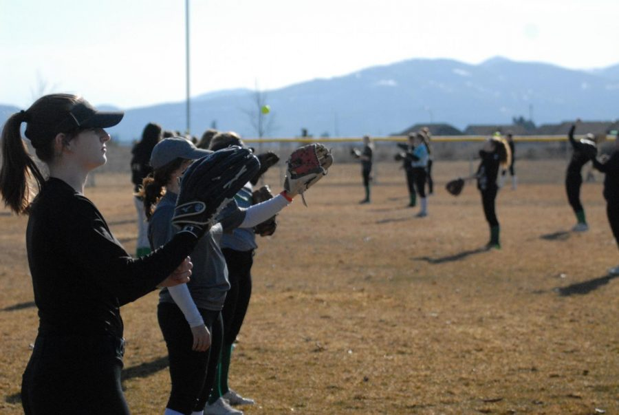Softball team warms up with catches during practice
