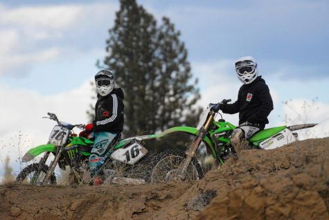 Dirt bike riders pose with their bikes on top of a hill at the Riverside State Park ORV park in 7 Mile, Washington