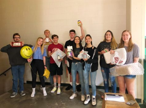 Mrs. Wenstrom's Physics class holding up their second egg drop projects before they drop them.