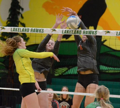 Bethany Johnson spike being blocked by two Moscow Players