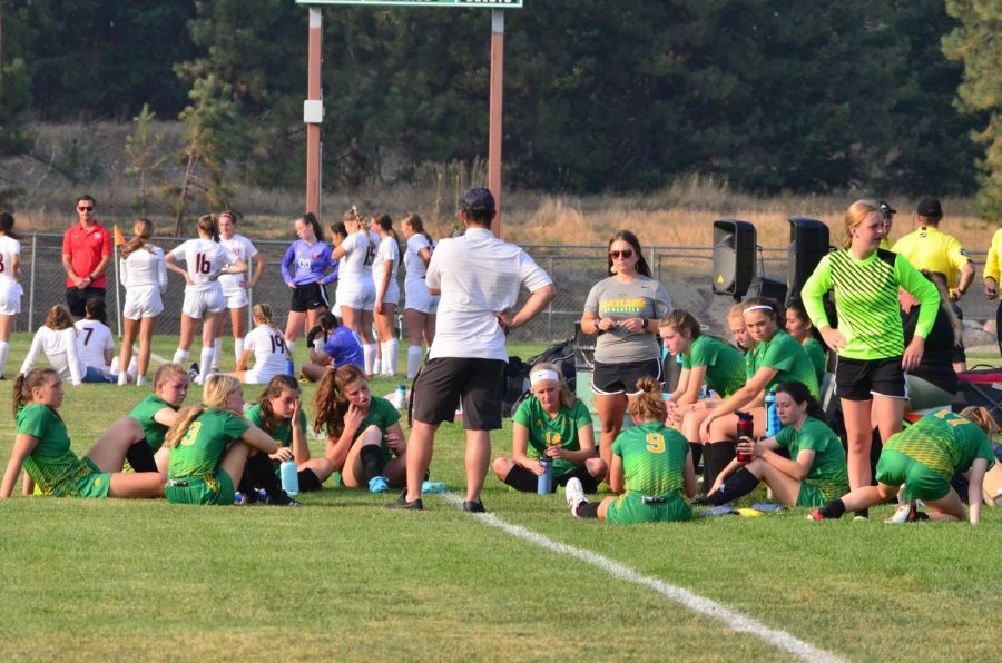 The Lady Hawks soccer team getting a pep talk from their coach before the game.